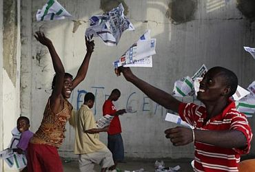 Haitians throw ballots into the air after frustrated voters destroy electoral material during a protest in a voting centre in Port-au-Prince