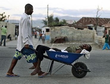 A Haitian with symptoms of cholera is transported in a wheelbarrow in the slums of Cite-Soleil in Port-au-Prince