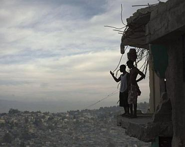 Orich Florestal (Left), 24 and Rosemond Altidon, 22, stand on the edge of their partially destroyed apartment of Port-au-Prince