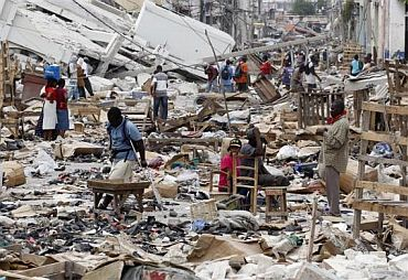 Residents walk in a destroyed area