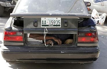 A dead victim is seen inside the boot of a car after the earthquake in Port-au-Prince