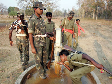Security personnel drink water while patrolling a forest area in Chhattisgarh