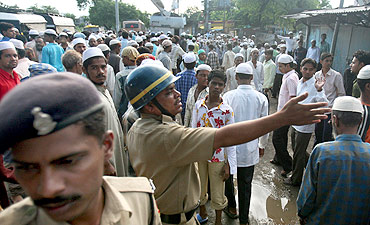 Policemen control a crowd gathered at a blast site outside a mosque in Malegaon