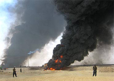 Paramilitary soldiers stand guard as plumes of smoke rise from a burning fuel tanker in Baluchistan
