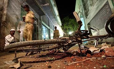 People walk past a damaged bicycle lying at a blast site inside a mosque in Malegaon