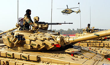Soldiers mounted on army tanks take part in the Army Day parade in New Delhi