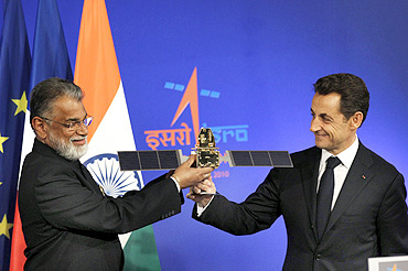 French President Nicolas Sarkozy receives a model of a satellite from ISRO Chairman Dr Radhakrishnan in Bengaluru