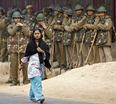 A girl walks pasts policemen during a demonstration