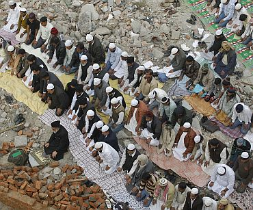 Muslims offer Friday prayers at the site of a demolished mosque