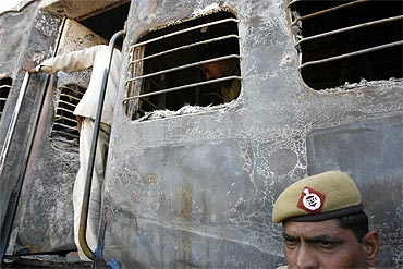 A policeman stands outside a burnt carriage of Samjhauta Express after the blast
