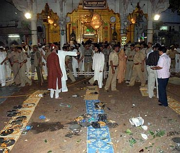 Security personnel and onlookers stand at the site of a bomb blast in Ajmer