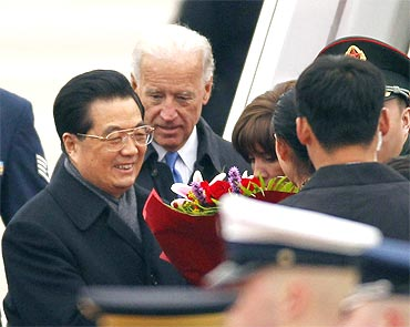 President Hu Jintao receives flowers upon his arrival at Andrews Air Force Base near Washington for a state visitUS Vice President Joe Biden is at rear