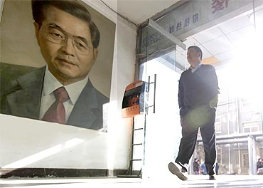 A man walks past a portrait of China's President Hu Jintao by artist Ye Zhifu outside a gallery in Beijing on Tuesday