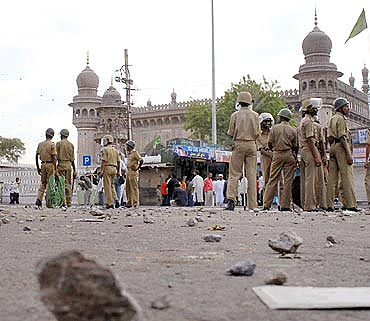 Policemen stand guard at the site of a blast in front of Mecca Masjid