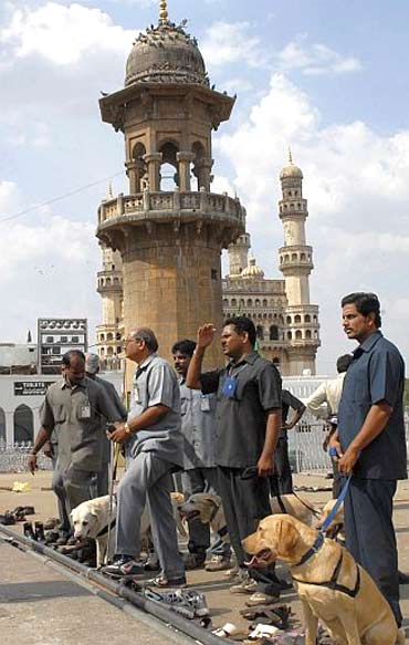 Policemen use sniffer dogs to inspect the site of a bomb blast at Mecca Masjid