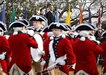 Barack Obama (R) and Hu Jintao watch a ceremonial marching band