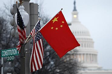 Chinese and American flags fly on a lamp post along Pennsylvania Avenue near the US Capitol