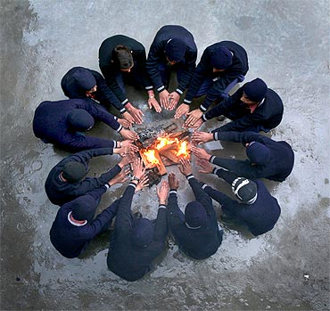 School children sit around a fire to warm themselves during their recess break inside a school in Jammu