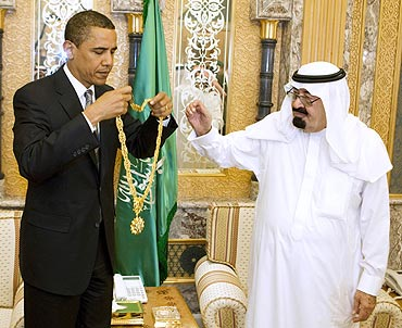 US President Barack Obama holds a gift he received from Saudi Arabia's King Abdullah during a meeting at the King's farm outside Riyadh