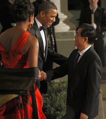 US President Barack Obama and first lady Michelle Obama greet China's President Hu Jintao as he arrives for a State Dinner in his honour at the White House