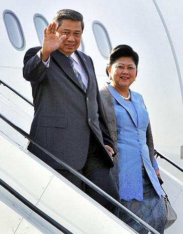 Indonesian President Susilo Bambang Yudhoyono waves beside his wife Kristiani Herawati upon their arrival at the New Delhi airport on Monday