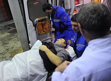 Medics wheel a victim of the bomb explosion at Domodedovo airport from an emergency vehicle into the N v Sklifosovsky Scientific Research Institute of First Aid in Moscow