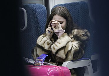 A woman cries while talking on the phone to an acquaintance who is at Domodedovo airport