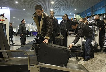 People entering Moscow's Domodedovo airport stand in line as they prepare to pass their belongings