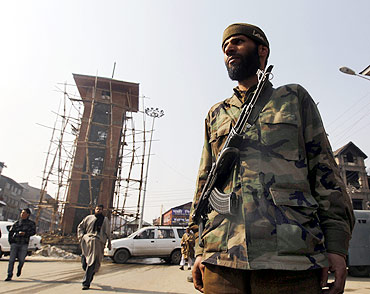 A policeman stands guard in front of Kashmir's clock tower at the historic Lal Chowk