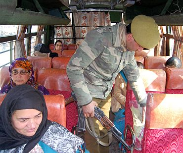 Security personnel conducting a search op in a bus