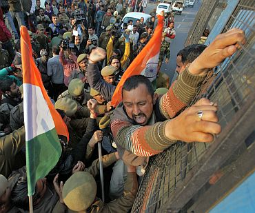A BJP supporter shouts as he is detained by police during a protest near Jammu airport