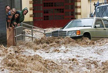 People look on as a street with vehicles is engulfed by heavy flooding in downtown Funchal, Madeira, Portugal, February 20, 2010.
