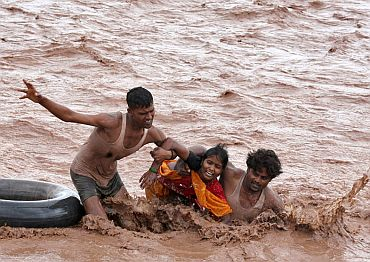 Rescuers help a woman to move a safer place from flooded Ghaghar river after heavy rains in Punchkula in the northern Indian state of Haryana September 8, 2010