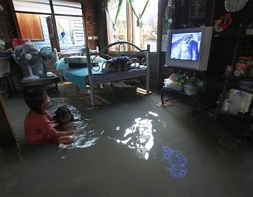 Residents watch television at their flooded house in Bangkok October 25, 2010