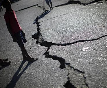 A child walks past a crack caused by the earthquake in a street in Port-au-Prince January 16, 2010