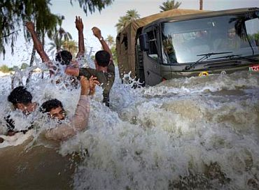Residents being evacuated through flood waters dodge an army truck carrying relief supplies for flood victims in Pakistan's Muzaffargarh district in Punjab province August 11, 2010