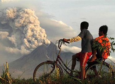 Boys look at the eruption of Mount Merapi volcano in Manisrenggo village, in the Klaten district of Indonesia's central Java province November 10, 2010