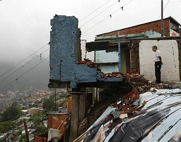 A man looks at a destroyed house in the low-income neighborhood of Catia in Caracas, Venezuela, December 1, 2010