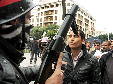 A riot policeman faces off with a protester during a demonstration in downtown Tunis