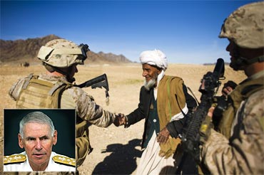 A US soldier interacts with an Afghan man. Inset: Admiral William J Fallon