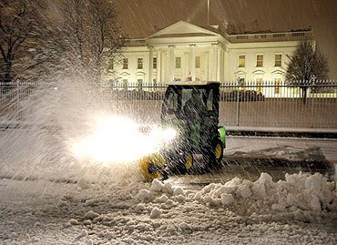 A snow plow works the front of the White House