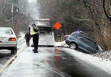 A tow-truck operator works on recovering a vehicle that went off the road after overnight snow and rain in Great Falls, Virginia