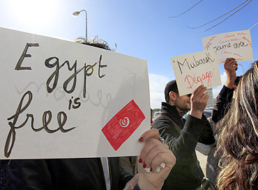 People hold signs during a protest in front of the Egyptian embassy in Tunis