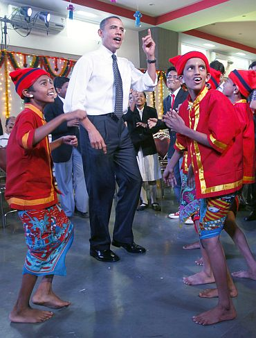 US President Barack Obama dances with children in a school in Mumbai