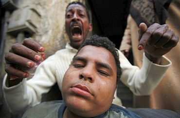 An anti-government protester reacts as his relative is injured during clashes with riot police in the port city in Suez