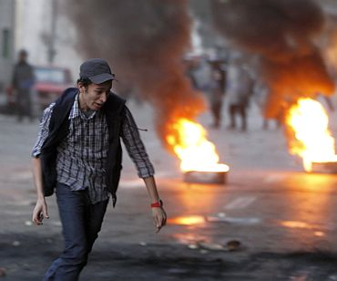 A protester runs in front of burning tyres placed to form a barricade during clashes with riot police in Cairo
