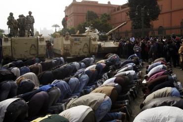 Protesters pray next to military personnel standing atop their vehicles in Cairo