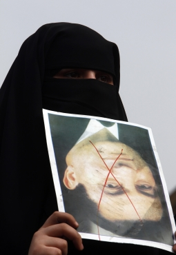A veiled protester holds a photo of Egypt's President Hosni Mubarak marked with an X, during a demonstration at Tahrir square in Cairo