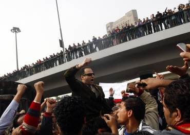 Egyptians carry an army officer who joined the protesters at Tahrir square in Cairo