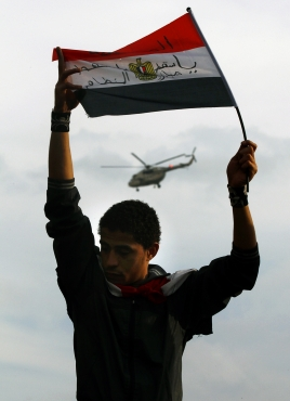 A protester holds an Egyptian flag as an army helicopter flies overhead